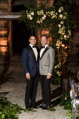 same-sex-wedding-gay-couple-groom-in-navy-tuxedo-jacket-groom-in-grey-tuxedo-jacket-under-arch