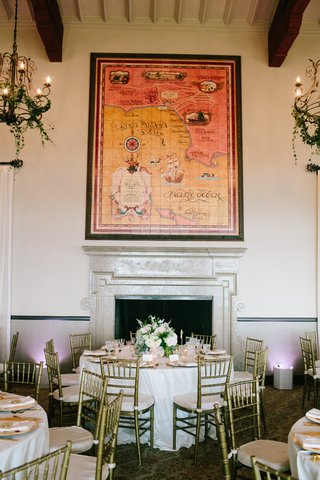 round-reception-table-with-low-centerpiece-in-front-of-fireplace-and-large-map-at-bel-air-bay-club