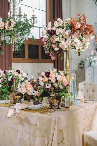 centerpiece-with-ranunculus-and-orchids-on-tall-golden-stand