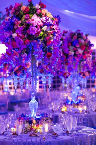 wedding-reception-centerpiece-of-crystal-candelabra-with-purple-orchids-and-red-and-yellow-roses