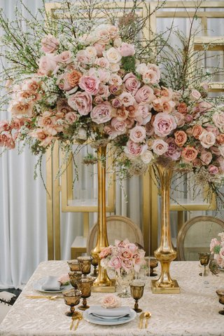 tall-floral-arrangements-with-roses-in-varying-shades-of-pink-and-greenery-in-gold-vase-taupe-linen