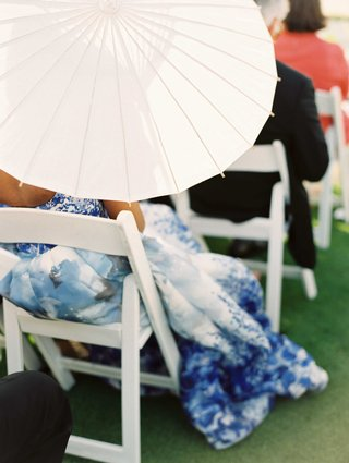white-sun-umbrella-parasol-being-held-by-ceremony-guest-in-white-chair-on-grass-lawn