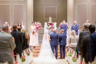 wedding-ceremony-church-cross-at-altar-white-pink-flowers-guests-pews-decorated-with-green-pink-deco