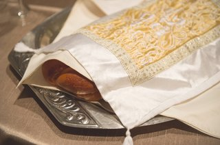 challah-draped-with-a-white-cover-with-gold-embroidery-on-silver-tray-for-a-jewish-wedding-reception