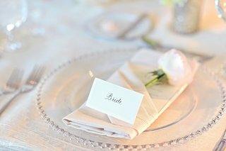 bride-escort-card-on-top-of-napkin-with-pink-rose