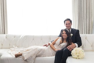 bride-in-eddy-k-couture-groom-in-calvin-klein-bride-leaning-on-grooms-lap-lying-on-couch
