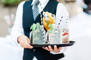 wedding-cocktail-hour-server-in-vest-tie-holding-tray-with-mason-jar-handle-cocktails-wine-glasses