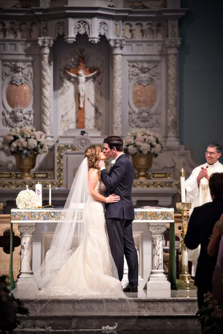 bride-and-groom-share-sweet-kiss-brides-hand-on-grooms-hip-ines-di-santo-veil-wedding-ceremony