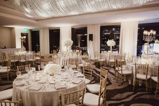 wedding-reception-ballroom-neutral-colors-white-flowers-gold-chairs-crystals-on-ceiling