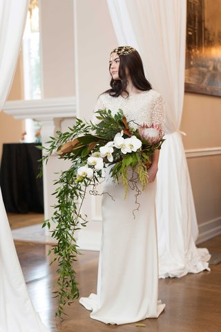 a-bride-with-a-headpiece-stands-with-a-large-cascading-bouquet-of-white-flowers-and-foliage