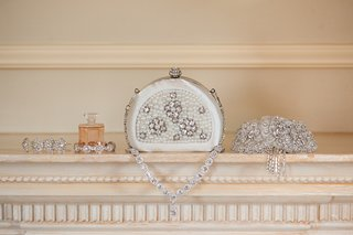 brides-satin-minaudiere-decorated-with-crystals-and-pearls-sits-next-to-sparkling-bracelets