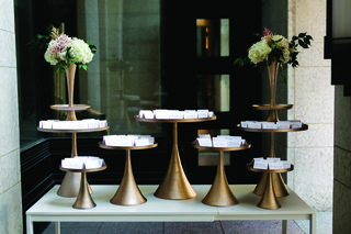 escort-cards-displayed-on-golden-stands-at-wedding-reception