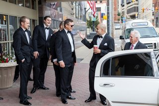 groom-with-friends-in-tuxedos-getting-into-white-sedan