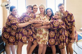 bride-in-white-floral-robe-and-bridesmaids-in-purple-flower-robes-in-bridal-suite-hugging