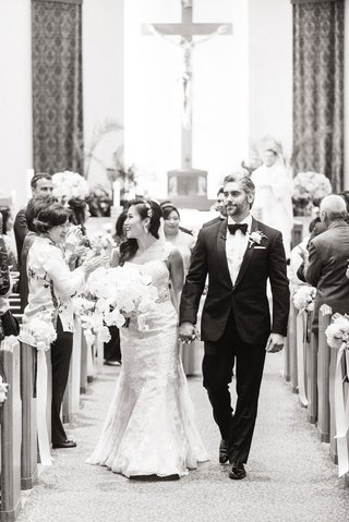black-and-white-photo-of-bride-and-groom-holding-hands-leaving-the-altar-newlyweds