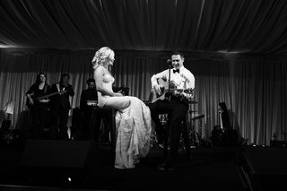 black-and-white-photo-of-bride-and-groom-on-stage-for-surprise-song-written-by-groom-to-bride
