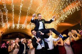 groomsmen-guests-lifting-groom-during-hora-jewish-wedding-reception-twinkle-lights-hanging-ceiling