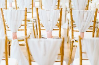 gold-chair-back-with-white-cushions-white-chair-cover-and-pink-fabric-wrap