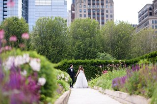 bride-in-monique-lhuillier-wedding-dress-ostrich-feather-skirt-with-groom-in-tuxedo-greenery-skyline