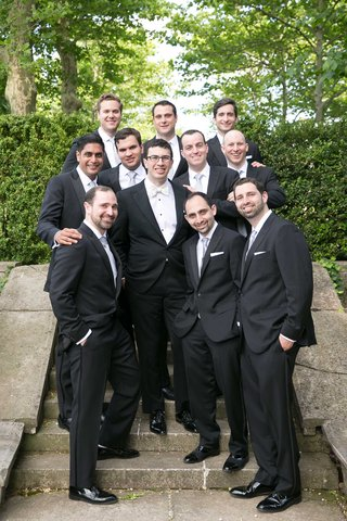 groom-in-tuxedo-with-white-bow-tie-and-groomsmen-in-tuxedos-with-silver-ties