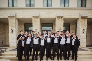 groom-and-groomsmen-in-tuxedos-in-front-of-texas-venue