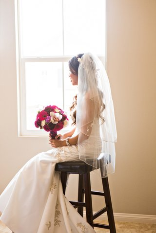 bride-sitting-at-window-in-veil-from-davids-bridal