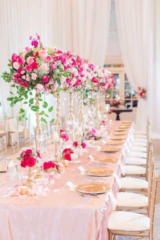 wedding-reception-long-table-pink-linen-gold-chairs-tall-risers-green-leaves-pink-rose-flowers