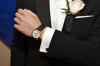 groom-in-black-tuxedo-with-blush-rose-on-lapel
