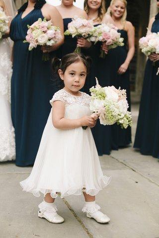 flower-girl-holding-large-bouquet-in-beaded-white-dress