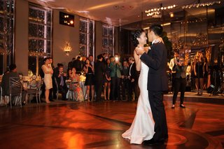 strapless-wedding-dress-dancing-with-groom-in-tuxedo-bride-smiling-guests-watching-and-taking-photo