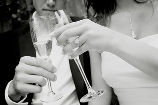 bride-and-groom-toast-champagne-christopher-designs-engagement-ring