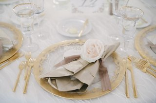 wedding-place-setting-of-gold-rimmed-clear-charger-champagne-flutes-gilt-flatware-napkin-and-rose