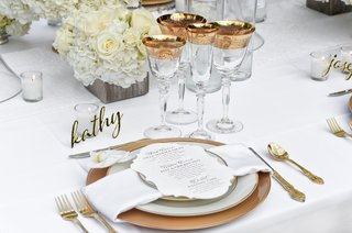 wedding-place-setting-with-gold-laser-cut-place-setting-gold-chargers-gold-flatware-and-an-orchid