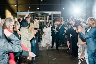 send-off-for-bride-and-groom-grand-exit-wedding-guests-wave-glow-sticks-confetti-and-streamers