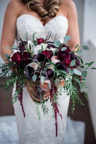 bride-in-sweetheart-neckline-wedding-dress-holding-dark-burgundy-bouquet-greenery-freshly-picked