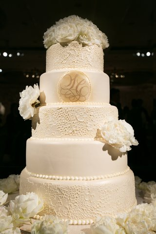 white-cake-with-lace-details-monogram-and-fresh-peonies