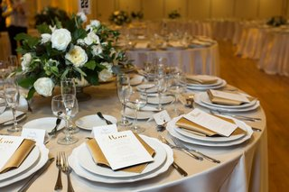 wedding-reception-low-centerpiece-with-greenery-and-white-flowers-champagne-linens-gold-napkins
