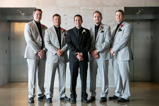 groom-in-all-black-ensemble-with-white-boutonniere-standing-groomsmen-in-grey-black-pink-boutonniere