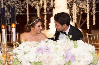bride-with-a-crystal-headband-stares-at-groom-in-black-tuxedo-at-head-table-with-white-purple-rose