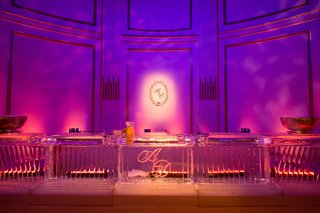 pink-and-purple-uplighting-behind-ice-bar-with-couples-initials-at-wedding-reception