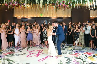 bride-in-strapless-dress-and-groom-in-blue-suit-dancing-on-colorful-dance-floor-as-guests-watch