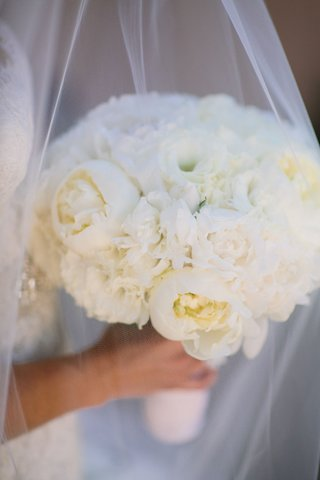 bride-holding-wedding-flowers-of-white-peonies