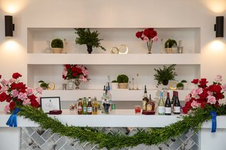 kentucky-derby-themed-bridal-shower-bar-with-garland-held-by-blue-ribbons-red-and-pink-roses
