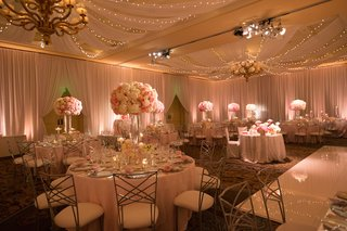 ballroom-reception-with-twinkle-lights-draping-and-tall-flower-arrangements