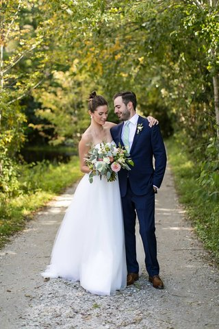 wedding-portrait-bride-in-strapless-wedding-dress-high-bun-bouquet-groom-in-suit-with-light-green-ti