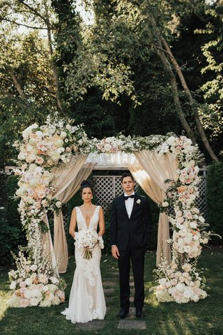 bride-and-groom-under-chuppah-drapery-white-pink-peach-flowers-greenery-plunging-v-neck-gown