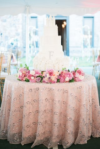 white-wedding-cake-inspired-by-cinderellas-caste-flowers-on-base-sparkling-linen