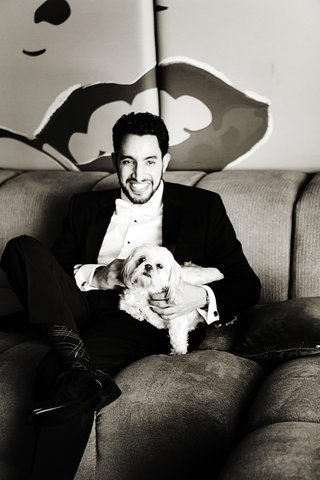 black-and-white-photo-of-groom-on-couch-holding-lap-dog-puppy