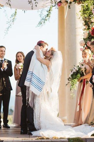 couple-shares-first-kiss-california-venue-jewish-garb-kippah-tallit-veil-pelican-hill-wedding