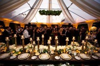 wedding-reception-guests-on-dance-floor-wood-table-greenery-chandelier-orbs
